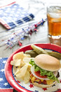 Loaded cheeseburger at a patriotic themed cookout is with ketchup mustard tomato onion and lettuce bbq it is served with potato Royalty Free Stock Photos