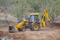 Loader backhoe digger at road construction site work on of india Royalty Free Stock Image