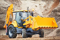 Loader excavator with risen shovel wheel bucket at eathmoving works in construction site or sandpit Stock Photos