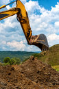 Loader excavator standing in sandpit with risen bucket over cloudy sky Stock Photography