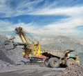 Loading of iron ore on very big dump body truck Royalty Free Stock Photo