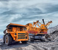 Loading of iron ore on very big dump body truck Stock Photos