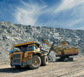 Loading of iron ore on very big dump body truck Royalty Free Stock Images