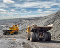Loading of iron ore on very big dump body truck Stock Image