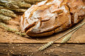 Loaf of bread in a rural bakery with wheat on old wooden table Stock Images