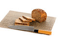 Loaf of wholemeal bread cutting into slices on wood bread board with knife isolated white background food Stock Photography
