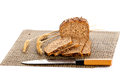Loaf of wholemeal bread cutting into slices on wood bread board with knife isolated white background healthy food nutrition Stock Image