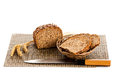 Loaf of wholemeal bread cutting into slices on wood bread board with knife isolated white background healthy nutrition Stock Photos