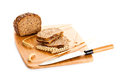 Loaf of wholemeal bread cutting into slices on wood bread board with knife white background healthy food nutrition Royalty Free Stock Photography