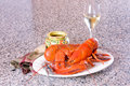 Lobster dinner pair of freshly cooked and a glass of wine on a plate over a granite contertop Stock Image