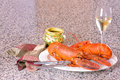 Lobster dinner pair of freshly cooked and a glass of wine on a plate over a granite countertop Royalty Free Stock Photos