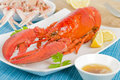 Lobster and langoustines with browned butter lemon wedges in background Stock Images