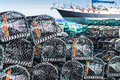 Lobster pots stacked against a fishing boat Royalty Free Stock Photo
