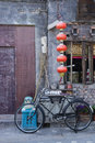 Local chinese hutong scene old beijing a homemade broom an overflowing blue garbage bin with lettering some flowerpots a bicycle Royalty Free Stock Photos