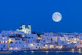 Local church of Naoussa village at Paros island in Greece against the full moon. Royalty Free Stock Photo
