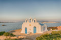 Local church in Pirgaki in Paros island against the blue Aegean sea. A beautiful landscape. Royalty Free Stock Photo