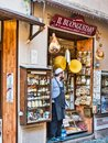 Local vendor waits for customers at the entrance of their business in the village of Orta San Giulio in Lake Orta Italy during a