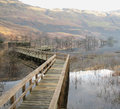 Loch lomond a walkway reaches out into the waters of on a quiet christmas eve morning there is a light mist obscuring the hills Royalty Free Stock Photo