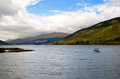 Loch tay in scotland side view with blue sky and dramatic clouds Royalty Free Stock Image