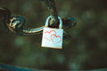 Lock with two hearts hanging on the railing.