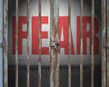 Locked door with red word fear on concrete wall Royalty Free Stock Photo