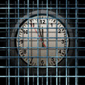 Locked schedule business concept and doing time behind bars with a time clock confined away in prison as a symbol of Stock Image
