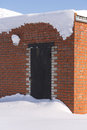 Locked shut metal door covered with snow. Brick wall building. Royalty Free Stock Photo