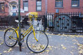 A locked yellow bike on the street we saw in soho Stock Images