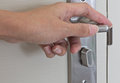 Locking up or unlocking door with hinge in hand Royalty Free Stock Photography