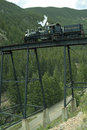 Locomotive on trestle bridge and above a mountain roadway Stock Photo