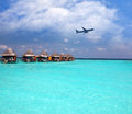 Lodges over water and the plane in sky tropical paradise Royalty Free Stock Photography
