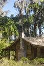 Log cabin under moss draped trees on Shingle Creek, Florida. Royalty Free Stock Photo