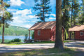 Log cabins in forest and on lake two red sit a surrounded by an evergreen Royalty Free Stock Photo