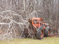 Logging tractor a used for sitting on the edge of a bush with a tree on it Stock Photos