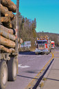 Logging trucks on highway with wood logs Royalty Free Stock Images