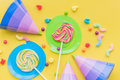 Lollipops and party hats for happy birthday on yellow background top view
