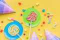 Lollipops and party hats for happy birthday on yellow background top view copyspace