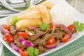 Lomo saltado traditional peruvian stir fry with beef red onions tomatoes and fries garnished with parsley and coriander Royalty Free Stock Image