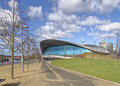 London aquatics centre image taken of the tree lined walk towards the with fluffy clouds and blue sky in the background Royalty Free Stock Photos
