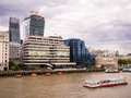 London bridge river thames view from across the to modern office buildings with a tourist cruise boat in the foreground Royalty Free Stock Image