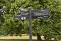 London directions signpost in kensington gardens park with for kensington palace princess diana memorial and serpentine Royalty Free Stock Photo