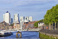 London docklands waterfront view canary wharf skyline over thames river along bankside with green trees and houses in late summer Royalty Free Stock Images
