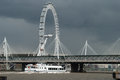 London eye against grey sky and golden jubilee bridge a dark april Royalty Free Stock Photography