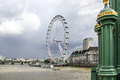The london eye from westminster bridge view of millenium wheel on a cloudy day on right a lamp post Royalty Free Stock Photos