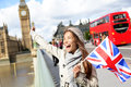 London happy tourist holding uk flag by big ben british and red double decker bus excited girl sightseeing travel on westminster Stock Photos