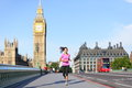 London lifestyle woman running near big ben female runner jogging training in city with red double decker bus fitness girl smiling Royalty Free Stock Images