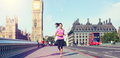 London lifestyle woman running near big ben female runner jogging training in city with red double decker bus fitness girl smiling Stock Images