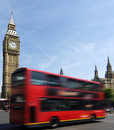 London red bus passing Big Ben Stock Image