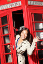 London red phone booth woman waving happy peaking out excited looking at camera saying hello beautiful smiling young female in Royalty Free Stock Photos