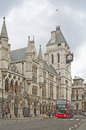 London royal courts of justice and red double decker in england Royalty Free Stock Photo